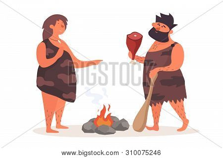 Primitive Man With Cudgel And Piece Of Meat Talks Beside Woman By Fire. Prehistoric People Dressed I