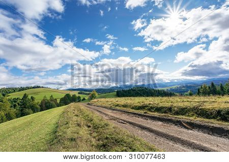 Dirt Road Through Hillside In Mountains. Beautiful Countryside Landscape In Early Autumn. Sunny Weat