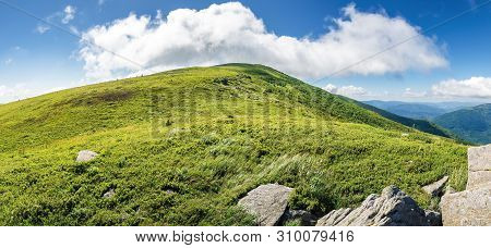 Beautiful Panoramic Landscape In Mountains. Rocks On The Grassy Slope. Cloud Above The Summit Of A H