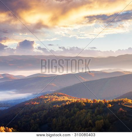 Sunrise In Mountains. Beautiful Autumn Landscape With Fog In The Valley. Ridge In The Distance View