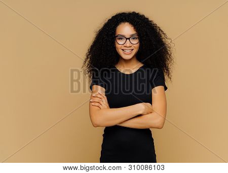 Slim Satisfied Woman With Afro Haircut, Wears Black Casual Clothes, Optical Glasses, Has Confident E