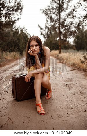 young beautiful girl in yellow dress with colorful scarf sitting on vintage suitcase on soaked muddy road after rain poster