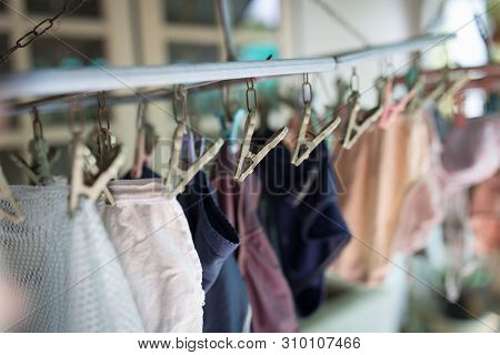 Clothes Pegs Or Clothespins Is Hanging The Underware On A Cord. Plastic Clothes Pegs On A Washing Li