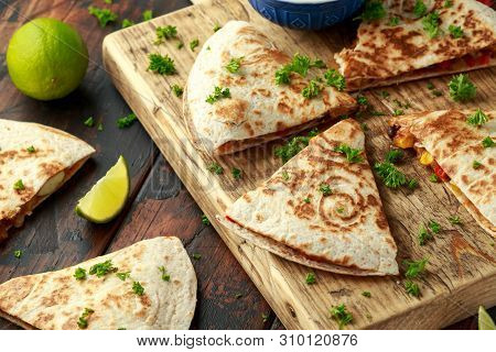 Mexican Quesadilla With Chicken, Corn, Black Beans, Cheese, Vegetables, Lime And Yogurt Sauce On Woo