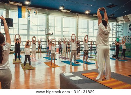Kyiv, Ukraine: Teacher And Yoga People Performing Simple Asanas Together, Training In Sport Class On
