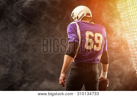 American Football Player Holding Ball In His Hands In Smoke. Black Background, Copy Space. The Conce