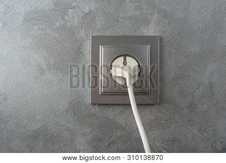 220 volt power plug on a stucco wall background poster