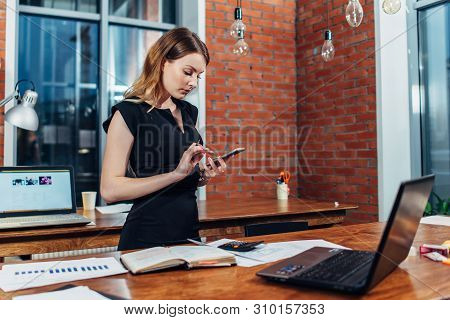Top View Of Woman Working Using Smartphone Standing At Her Workplace In Creative Office