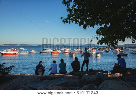 Istanbul, Turkey: View Of Resting Friends At Beach Of The Marmara Sea In Sunny Summer Day Located In