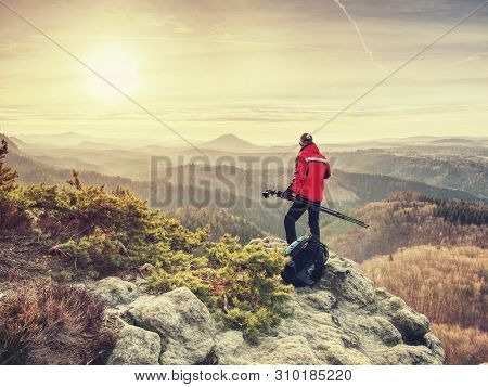 Photographer On Cliff With Tripod In Hand. Nature Photographer Will Take Photos With Mirror Camera O