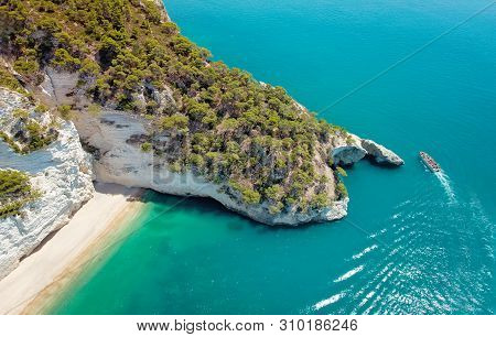Aerial View Of A Boat With Tourists Visiting A Groat Puglia Coast, Italy. Italian Holidays In Puglia