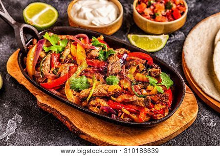 Fajitas With Colored Pepper And Onions, Served With Tortillas.