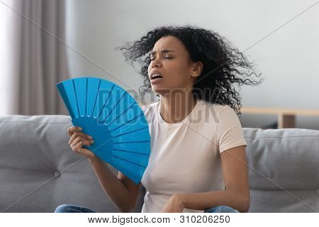 Overheated African Young Woman Feeling Hot Waving Fan At Home