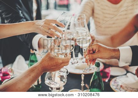 Hands Toasting With Champagne Glasses At Wedding Reception Outdoors In The Evening. Family And Frien