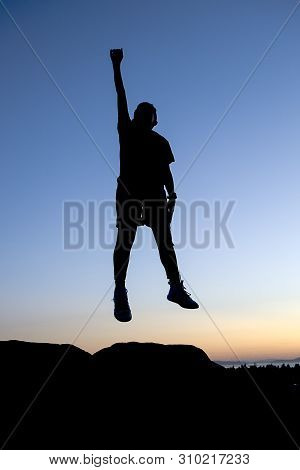Concept Image Of Boy Leaping In The Air.a Boy In Silhouette Of Sunset Leaps In The Air At Anacortes,