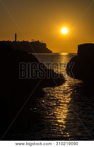The Lighthouse And The Sea In Front Of Porto Colom At Sunrise