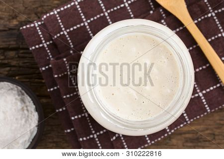 Fresh homemade bubbly sourdough starter, a fermented mixture of water and flour to use as leaven for bread baking, in glass jar with flour and wooden spoon on the side, photographed overhead (Selective Focus, Focus on the top of the starter) poster