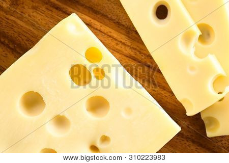 Piece And Slices Of Emmental, Emmentaler Or Emmenthal Cheese, Photographed Overhead On Wood
