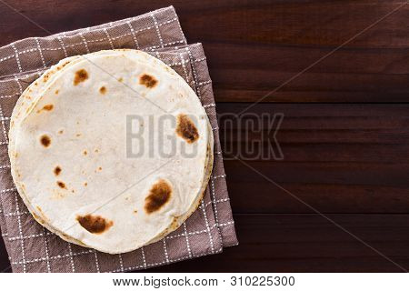 Fresh Homemade Flour Tortillas Piled On Kitchen Towel, Photographed Overhead With Copy Space On The