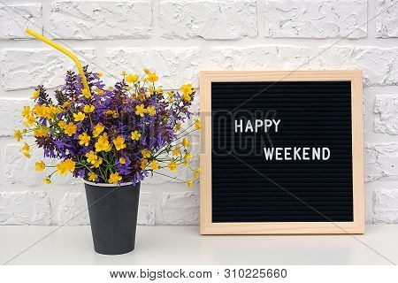 Happy Weekend Words On Black Letter Board And Bouquet Of Colored Flowers In Black Paper Coffee Cup W