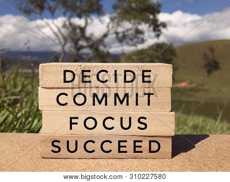 Motivational And Inspirational Wording - Decide, Commit, Focus, Succeed Written On Wooden Blocks. Bl