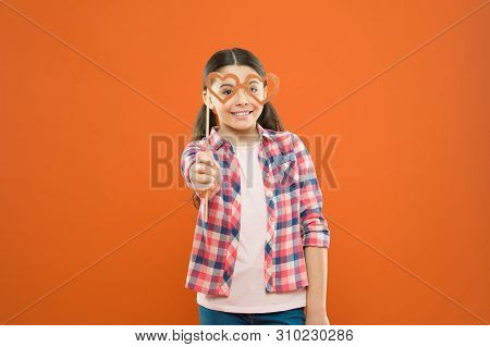 Fun Valentines Props. Cute Kid Smiling With Fancy Party Props On Orange Background. Funny Small Girl