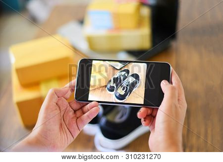 Young Woman Taking Photo Sneakers With Camera Smartphone For Post To Sell Online On The Internet Mar
