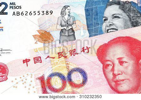 A red, Chinese one hundred yuan renminbi bank note with a blue two thousand peso note from Colombia close up in macro poster