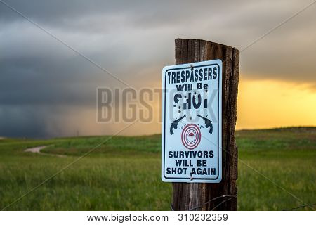 A No Trespassing Sign Riddled With Bullet Holes Reads: Trespassers Will Be Shot. Survivors Will Be S