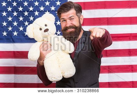 Looking For Fun Party Games. Party Man With Teddy Bear Pointing His Finger On American Flag Backgrou