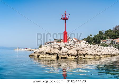 Red Lighthouse In Podgora Village And Adriatic Sea Bay, Croatia