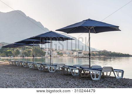 Parasols And Deck Chairs On The Beach In Baska Voda, Croatia