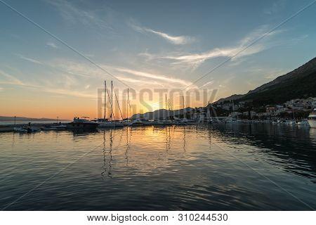 Beautiful Sunset In Baska Voda Town With Adriatic Sea And Boats, Croatia