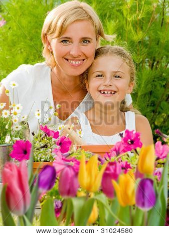 Spring garden, planting concept - mother and daughter working in flowers garden
