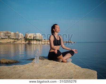 Woman meditating near water on Gozo island