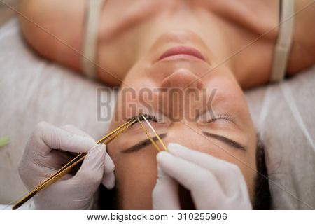 Procedure of eyelash extension in salon by cosmetician poster