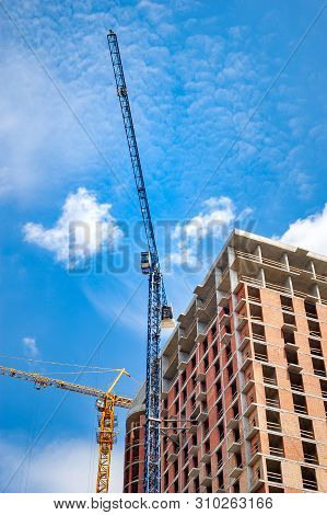 Construction Site With Cranes Near The House Against The Blue Sky With White Clouds. Construction Of