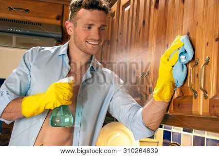Sexy Man Wearing Yellow Rubber Gloves Cleaning Kitchen