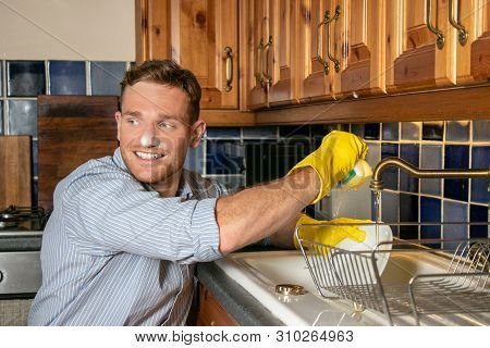 Handsome Young Man Washing Dishes In Kitchen