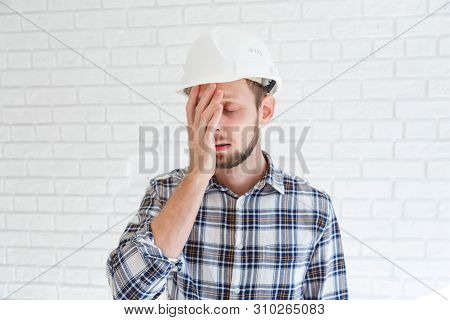 A Blue Collar Worker Wearing A Hardhat Is Covering His Face With His Hand