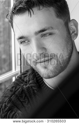 Portrait Of Handsome Man With Beard Sitting In Window