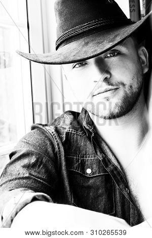 Portrait Of Handsome Cowboy Wearing Hat Sitting In Window