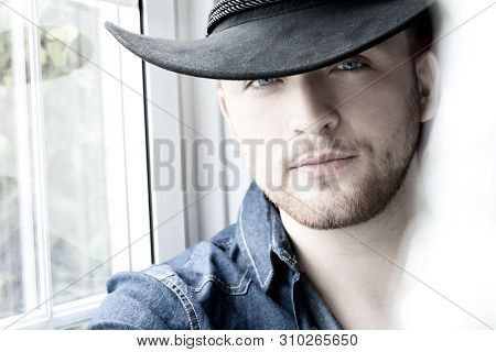Portrait Of Hot Male Cowboy Wearing Hat Sitting In Window