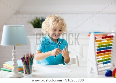 Child Doing Homework At Home. Little Boy With Wooden Colorful Abacus Doing Math Exercise Learning Ad