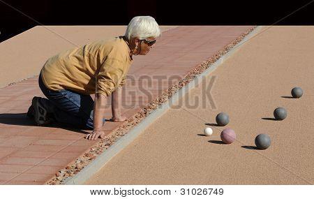 Senior Woman Studying Bocce Balls On Sand Court