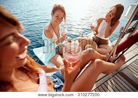 Smiling girl having party on sailing boat and drinking wine