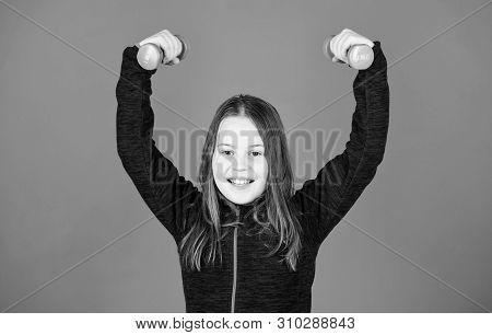 Toward stronger body. Girl exercising with dumbbell. Beginner dumbbell exercises. Child hold little dumbbell blue background. Sport for teens. Easy exercises with dumbbell. Rehabilitation concept poster