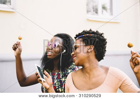 cool girlfriends with lollipop listening to music on headphones in city