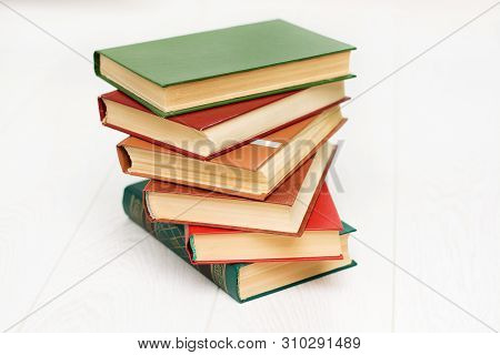 Stack Of Books Is Lying On A White Wooden Table. Green, Red And Brown Covers.