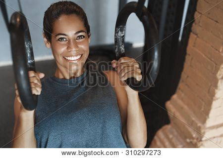 Close-up Satisfied Sweaty Attractive Smiling Woman Doing Crossfit Gymnastic Rings Exercise Push-ups,